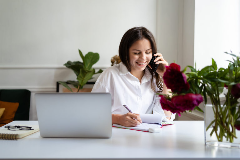 Happy woman sitting at desk on her phone and using her laptop