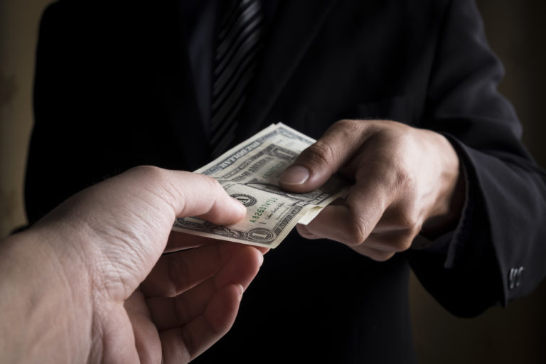 Man in suit hands person stack of money