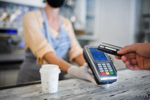 A person swipes their debit card at a cafe counter. Opted-in credit union accounts may overdraft and be charged a courtesy pay fee.