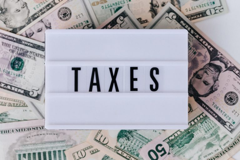 """Photo shows a sign reading """"taxes"""" on a pile of money, illustrating how people can still claim their stimulus check payments on their 2020 tax refund."""