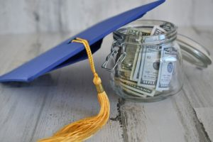 A photo shows a graduation cap and a jar of money. With student loan cancellation on the docket, many Americans have the opportunity to make a dent in their credit card debt.