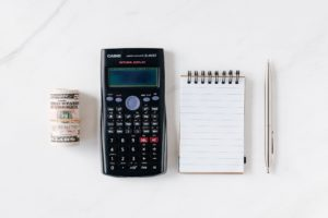 A photo shows a calculator, a pen and paper, and a roll of money. Before doing a balance transfer, you should calculate whether it is the best financial decision for you.