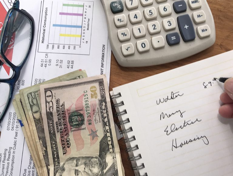 Person paying bills with spreadsheet, calculator, and stack of money