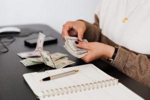 Person at desk counting money with open notebook