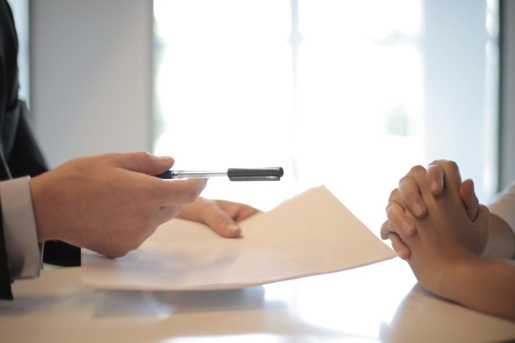 Person handing pen and paper to someone to sign