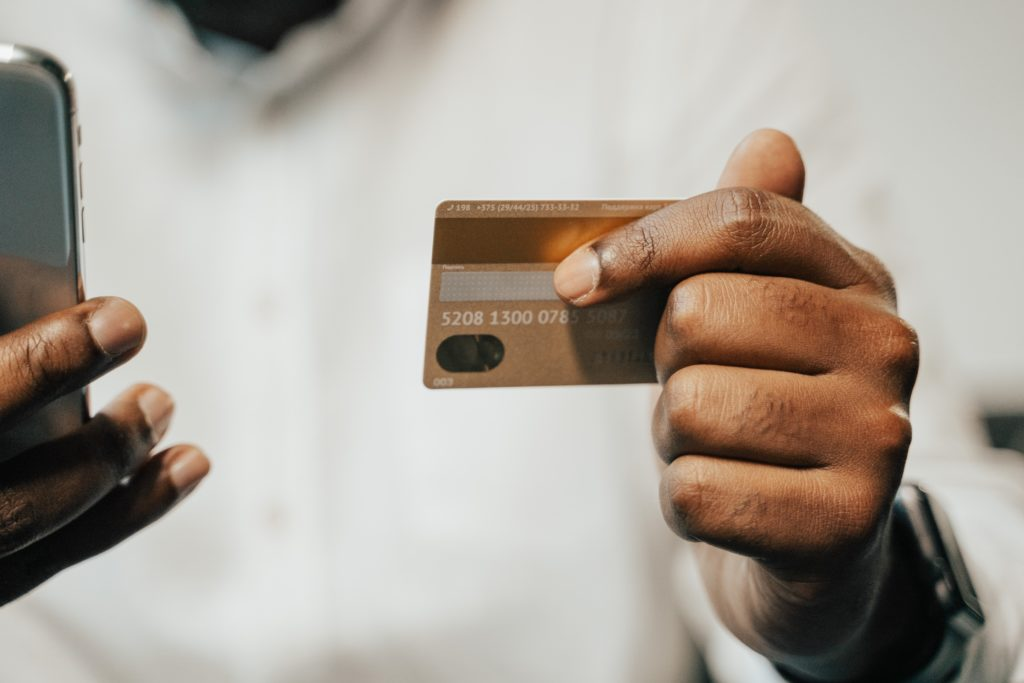 Man puts credit card number into mobile phone to purchase something
