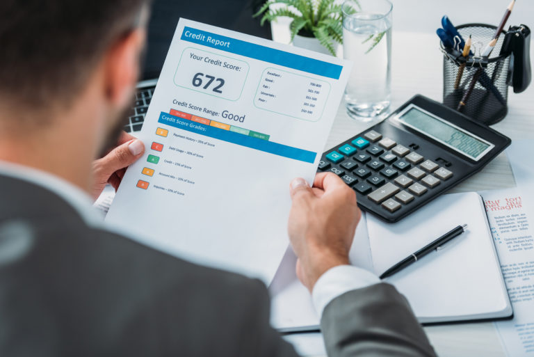 Man holds paper displaying credit report and credit score over desk covered in supplies