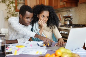 Couple sits at kitchen table paying bills online