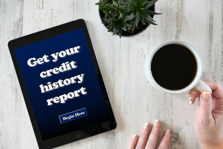 """Person holds cup of coffee next to tablet screen that reads """"Get your credit history report."""""""