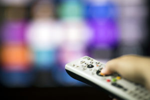Television remote points at blurred television screen with various streaming service logos