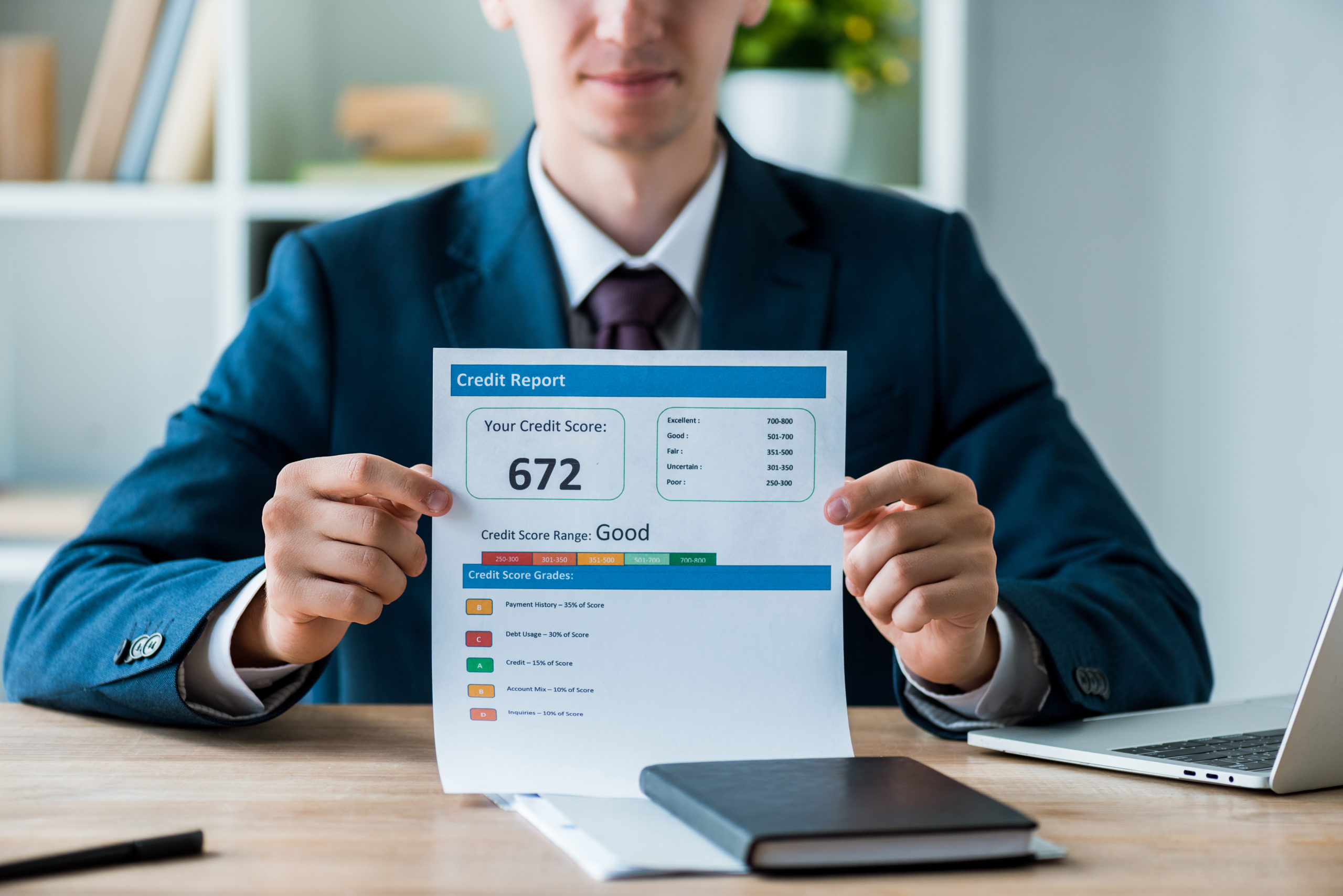 Man dressed in a suit sits behind a desk holding a credit score ranking as good