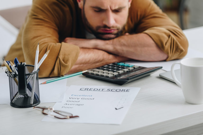 Sad man rests his head on crossed arms on top of a dash. Piece of paper lays in front of him showing a poor credit score.
