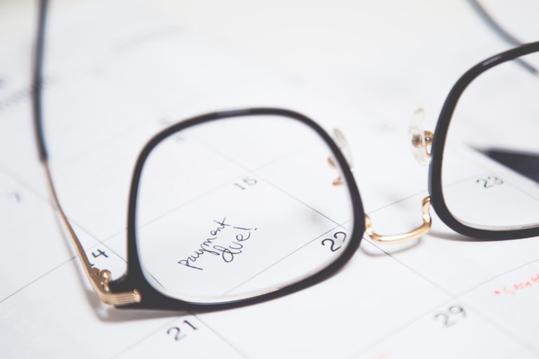 """Pair of reading glasses lay on top of a calendar with one day in focus that reads """"payment due."""""""